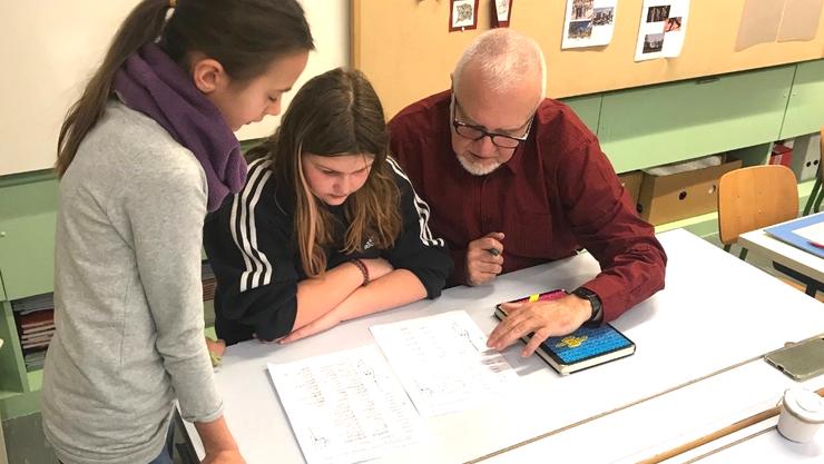 Senior im Unterricht mit Schülerinnen am Aufgaben besprechen