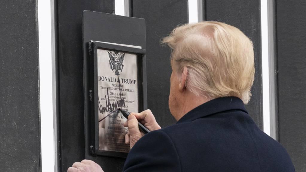 Donald Trump unterzeichnet eine Plakette an einem Abschnitt der US-Mexiko-Grenzmauer.