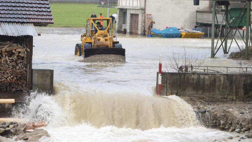 Wasser in Wolhusen LU: Mit einem Bagger werden nach einem Felssturz Geröll und Wasser entfernt.
