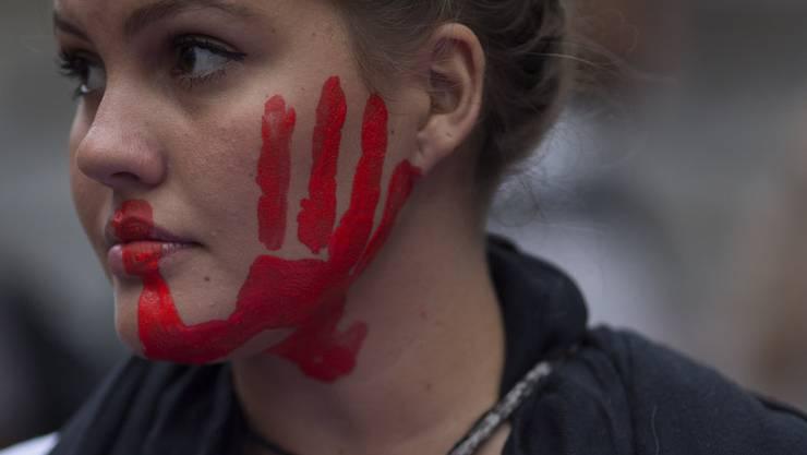 Diese Brasilianerin protestiert mit dem roten Handabdruck gegen Gewalt an Frauen.