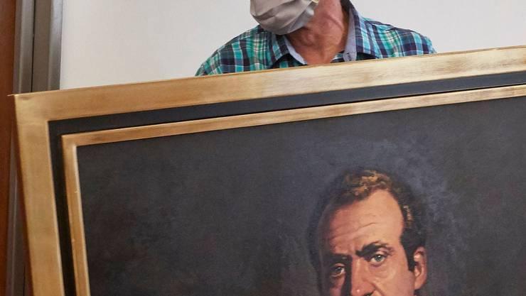 Ein Arbeiter transportiert ein Porträt von Juan Carlos ab.