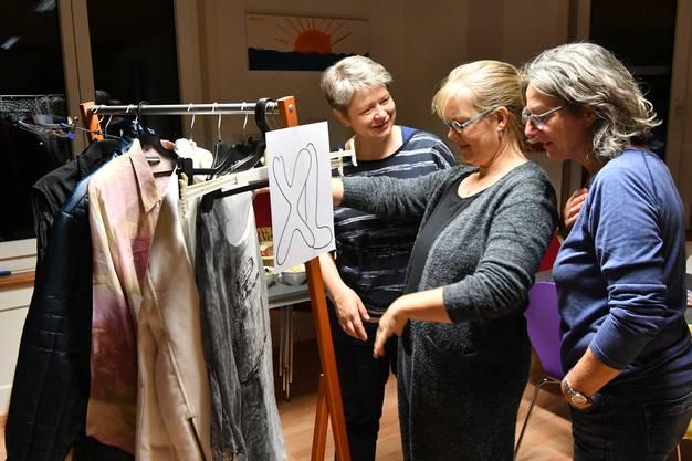 Die Organisatorinnen Cornelia Mackuth (links) und Corinne Etter (Mitte) begutachten mit einer Besucherin die herbstlichen Kleidungsstücke.