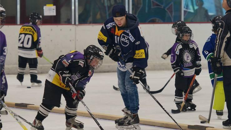 EVZ-Spieler Dominik Volejnicek und die kleinen Reinacher Eishockeyaner.