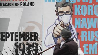 Ein Passant geht an einem Plakat (r) vorbei, das vor einer Vernachlässigung der Symptome einer Corona-Infektion warnt. Foto: Czarek Sokolowski/AP/dpa