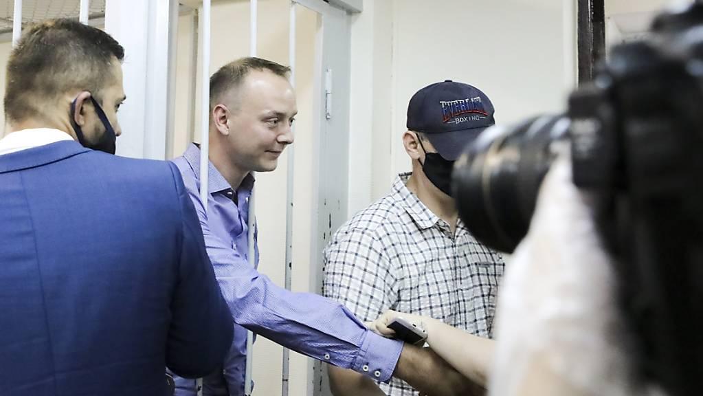 Iwan Safronow steht in einem Gerichtssaal in Moskau hinter Gittern und schüttelt einem Unterstützer die Hand. Foto: Sofia Sandurskaya/Moscow News Agency/AP/dpa