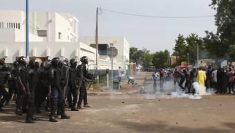 Die Polizei geht am Samstag mit Tränengas und Schlagstöcken gegen Demonstranten in Bamako in Mali vor.