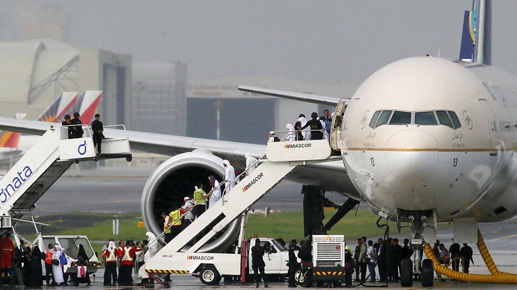 Nach der Entwarnung können die Passagiere begleitet von Sicherheitskräften das Flugzeug verlassen.