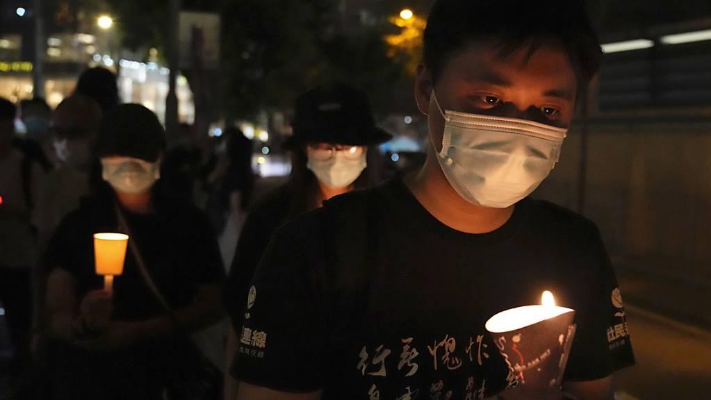 Menschen gehen mit Kerzen in den Händen vor dem Victoria Park entlang. Bereits in den vergangenen Jahren hatten sich dort etliche Menschen zum Jahrestag der blutigen Niederschlagung der Demokratiebewegung am 4. Juni 1989 in Peking versammelt.