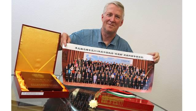 Ruedi Nützi inmitten der aus China mitgebrachten Award-Insignien: Es gab vom Anlass genau zwei Bilder (eines davon hält er in Händen), eine Medaille und die in englischer und chinesischer Schrift abgefassten Awardtafeln, eingelassen im Holzkistchen (links im Bild).