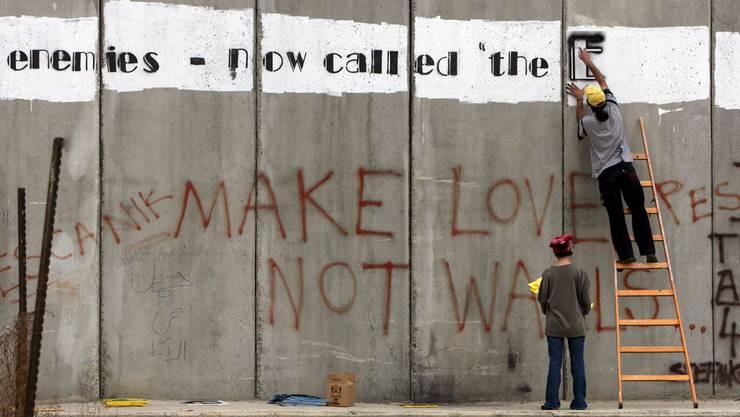 Friedensaktivisten bemalen die Grenzmauer zwischen Gaza und Israel. (Archiv)