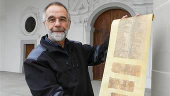Walter Ehrensperger mit einer Schriftrolle des Osterspiels von 1971 vor der Klosterkirche Muri. BA