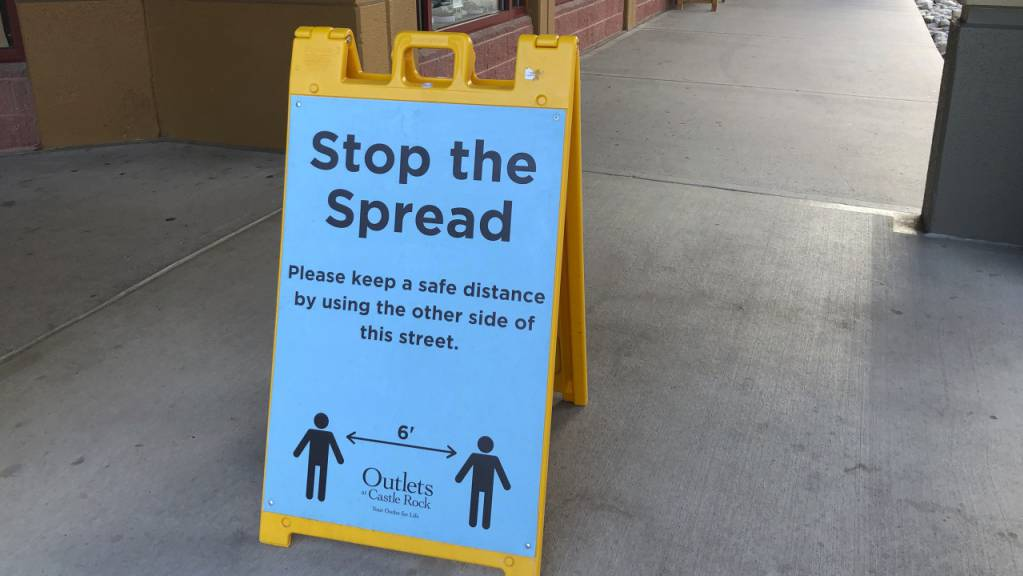 Ein Schild vor einem Einkaufszentrum im US-Bundesstaat Colorado weist Kunden darauf hin, Abstand zu halten, um die Verbreitung des Coronavirus einzudämmen.