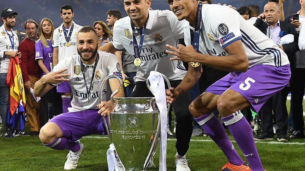Enzo Zidane (Mitte) feiert mit Benzema (l.) und Varane den Champions-League-Titel mit Real Madrid.