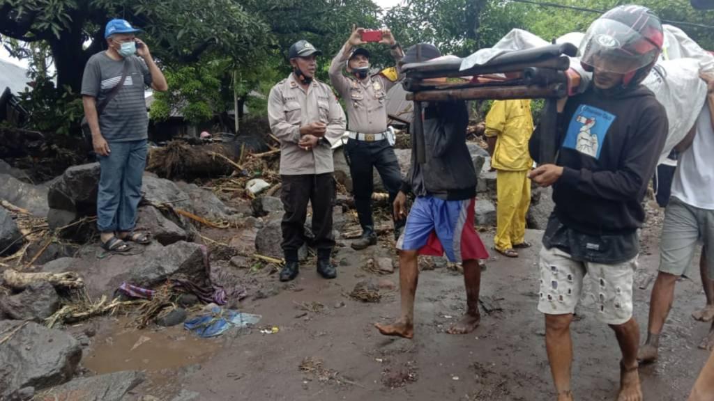 dpatopbilder - Menschen tragen einen Mann, der während einer Überschwemmung verletzt wurde. Foto: Ricko Wawo/AP/dpa