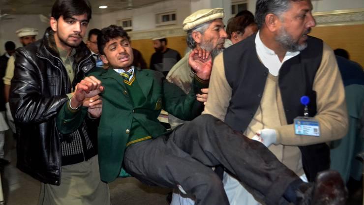 Ein verwundeter Schüler wird weggebracht.