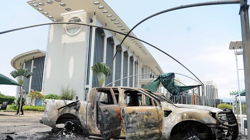 Ein ausgebranntes Auto vor einem Regierungsgebäude in Gabuns Hauptstadt Libreville.