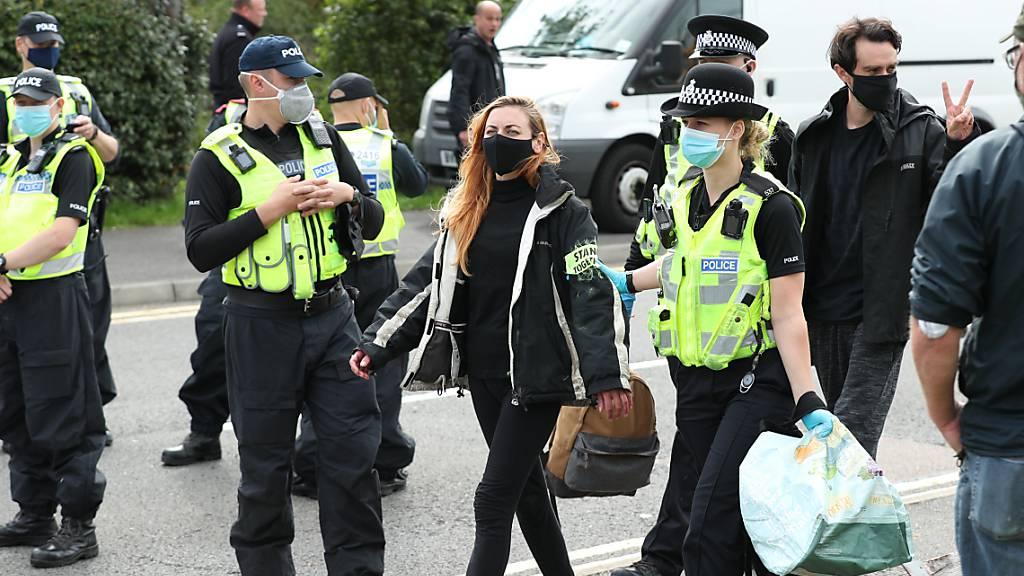 Eine Demonstrantin wird von einer Polizistin abgeführt, nachdem sie mit anderen eine Druckerei blockiert hatte. Viele Briten haben nach neuen Protesten der Umweltbewegung «Extinction Rebellion» am Samstag ihre Tageszeitung vermisst. Mehr als 100 Aktivisten hatten zuvor die Zufahrtsstraßen zu Druckereien blockiert. Foto: Yui Mok/PA Wire/dpa