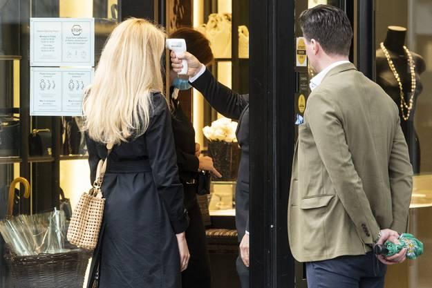 Einer Frau wird beim Einkaufen in einem Modebetrieb in Zürich die Temperatur gemessen. (Symbol)