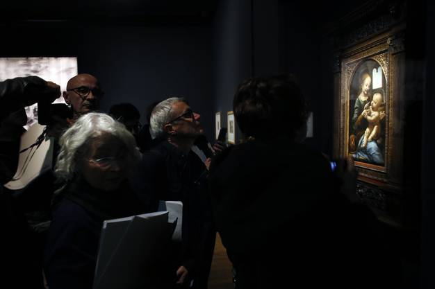 "Journalists watch the painting ""Benois Madonna"" by Leonardo Da Vinci, at the Louvre museum, in Paris, Tuesday, Oct. 22, 2019. The Louvre, the home of the ""Mona Lisa,"" is commemorating the 500th anniversary of Leonardo Da Vinci's death with a landmark new exhibit. (AP Photo/Thibault Camus)"