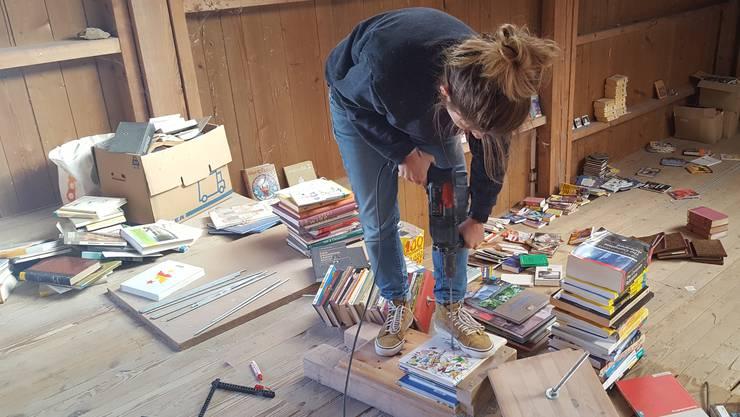 Naida Iljazovic (29) bohrt ein Loch durch den Bücherstapel.