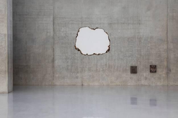 Angesengtes Papier als Leerstelle an der Wand und Boxen aus Bronze.