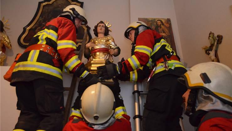Merenschwander Feuerwehrleute retten vorsichtig die Statue des heiligen Sebastian aus der Sakristei. ES