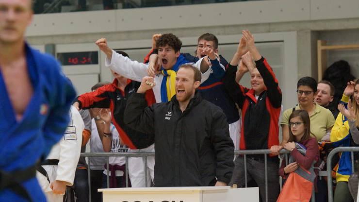 Martin Nietlispach freut sich zusammen mit seinen Kämpfern an seinem Coachingpult.
