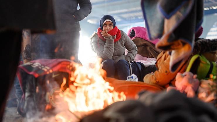 ARCHIV - Eine Frau aus Syrien sitzt an einem Lagerfeuer in einer leeren Markthalle nahe der türkisch-griechischen Grenze. Foto: Mohssen Assanimoghaddam/dpa