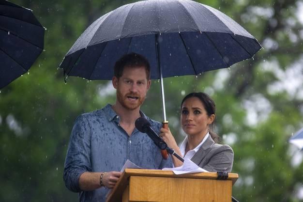 ....mühte sich seine Ehefrau Meghan, die Tropfen mit einem schwarzen Regenschirm von ihrem Gatten fernzuhalten.