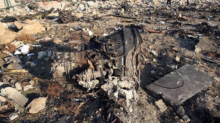 Einer der Flugzeugmotoren der abgestürzten Boeing 737 der Fluggesellschaft UIA liegt zwischen den Trümmern in der Nähe der iranischen Hauptstadt Teheran. Im Hintergrund arbeiten Ermittler an der Aufklärung der Unglücksursache.