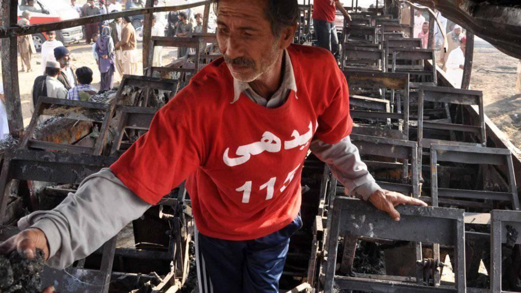 Überresten eines Busses nach Bombenexplosion in Pakistan: Beim jüngsten Anschlag sterben mindestens 15 Menschen. (Archiv)