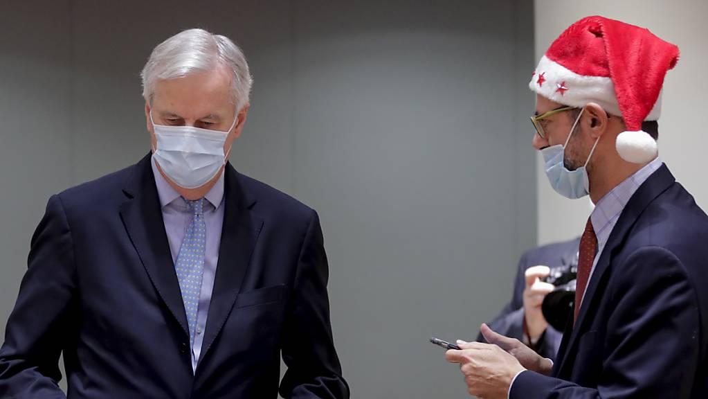 dpatopbilder - Michel Barnier (l), EU-Chefunterhändler für den Brexit aus Frankreich, trägt einen Ordner mit dem Brexit-Handelsabkommen neben einem Kollegen, der eine Weihnachtsmannmütze trägt, während einer Sondersitzung im EU-Hauptquatier. Foto: Olivier Hoslet/Pool EPA/AP/dpa