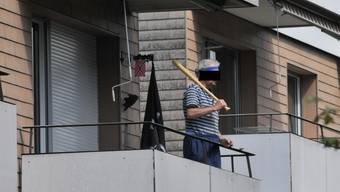 R.W. mit einem Baseballschläger auf seinem Balkon.