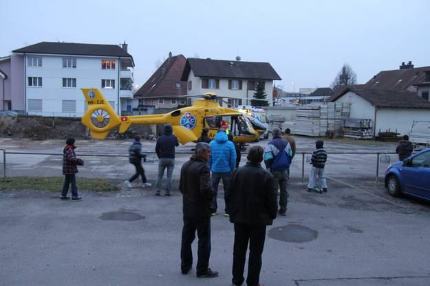 Schaulustige beobachten, wie die Rettungssanitäter schnellstmöglich die Frau ins Uni-Spital fliegen