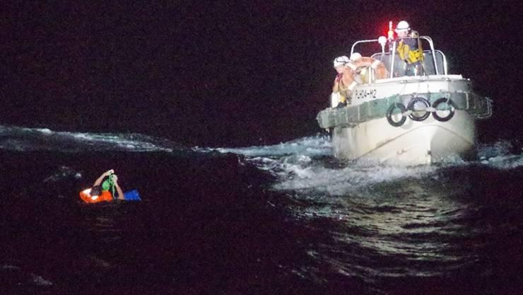 HANDOUT - Ein philippinisches Besatzungsmitglied eines panamaischen Frachtschiffes wird von Mitgliedern der japanischen Küstenwache aus dem Ostchinesischen Meer gerettet. Ein Frachter mit 43 Besatzungsmitgliedern und rund 5800 Rindern an Bord gilt vor dem Südwesten Japans als vermisst. Foto: Uncredited/The 10th Regional Japan Coast Guard Headquarters/AP/dpa - ACHTUNG: Nur zur redaktionellen Verwendung im Zusammenhang mit der aktuellen Berichterstattung und nur mit vollständiger Nennung des vorstehenden Credits