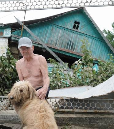 Mann mit Hund vor seinem zerstörten Haus.