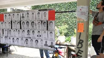 Eine Tafel zeigt die Bilder der 43 verschleppten Studenten.