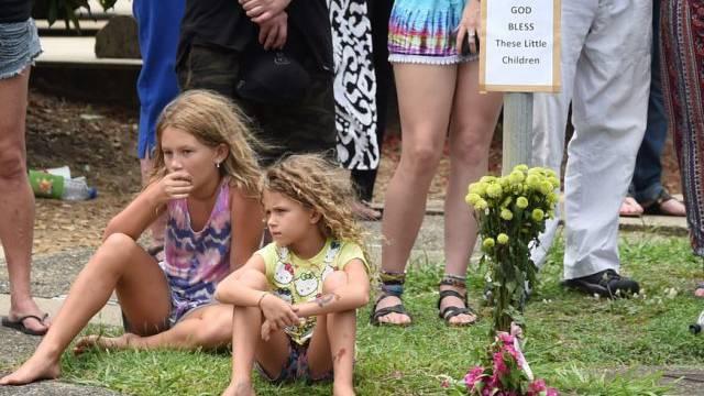 Kinder sitzen während der Prozession in Cairns am Strassenrand