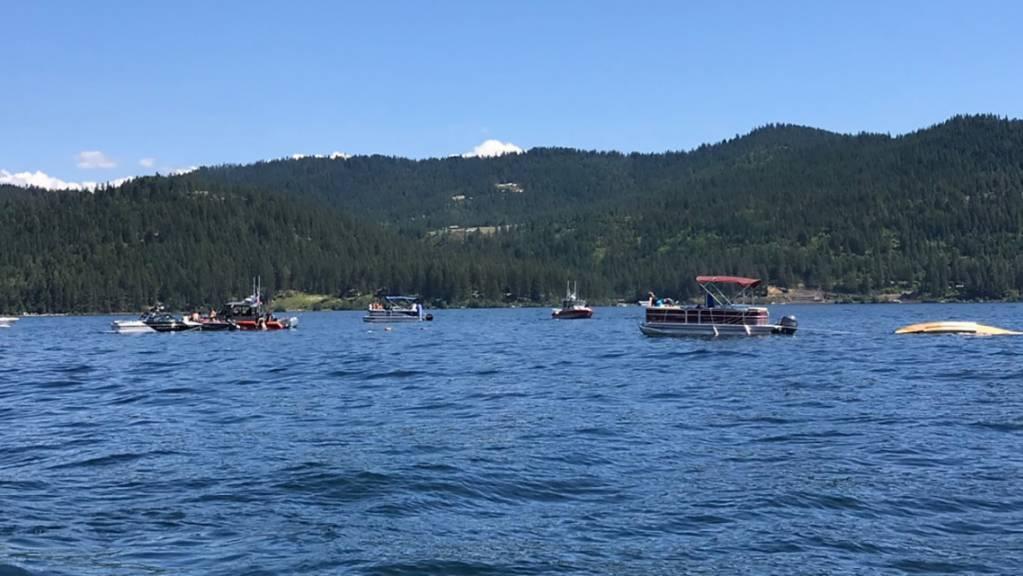 Boote sind in der Buch von Powderhorn am See Coeur d'Alene Nahe der Absturzstelle eines Wasserflugzeugs (rechts). Mindestens zwei Menschen sind beim Zusammenstoß zweier Kleinflugzeuge über einem See im US-Bundesstaat Idaho ums Leben gekommen.