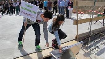 Schüler verewigen sich mit einer Zeitkapsel im Fundament des Schulhaus Reitmen.
