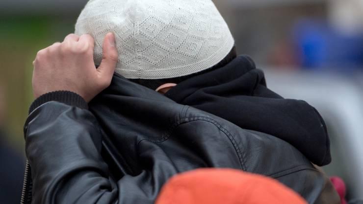 """Harmloser Zivilist oder Gefährder? Ein Mann aus dem Umfeld der Koran-Verteilaktion """"Lies"""" verdeckt in Frankfurt am Main mit seiner Jacke sein Gesicht. (Archiv)"""