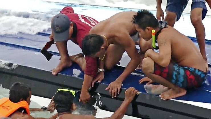 Helfer versuchen Touristen aus einem gekenterten Boot zu bergen. Bei dem Unglück starben mindestens drei Menschen.