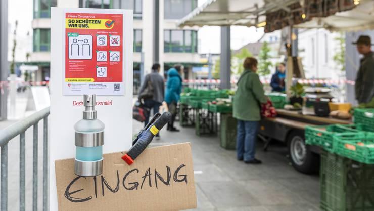 Spender mit Desinfektionsmittel und gut markierte Wege helfen beim sicheren Marktbesuch.
