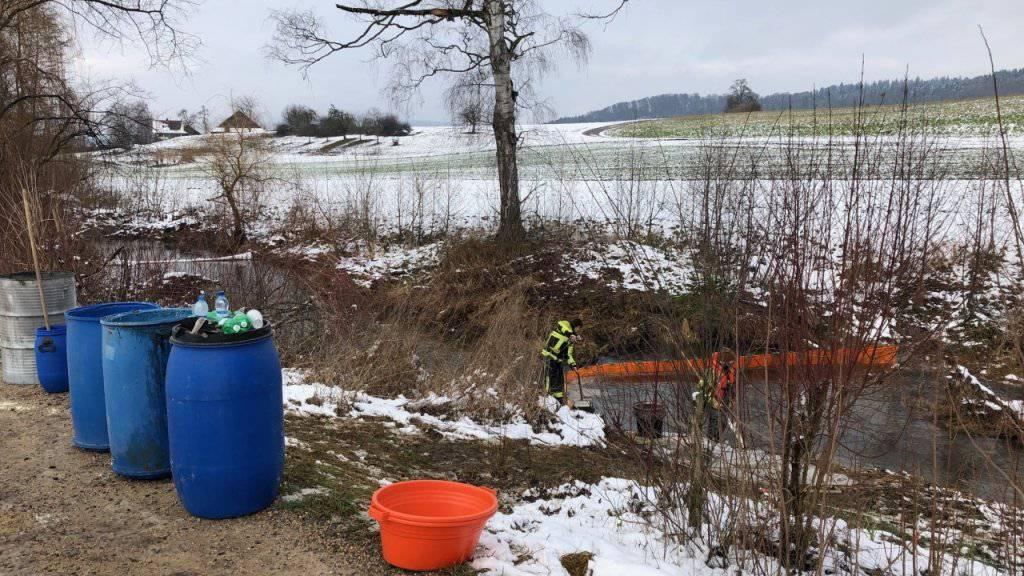 Feuerwehrangehörige errichten eine Ölsperre in der Bünz.