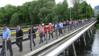 Über die Cartaseta-Brücke fand die Prozession der Waldgänger wieder zurück aufs Niedergösger Inseli (Zweiter von links: Bürgergemeindepräsident Patrick Friker).
