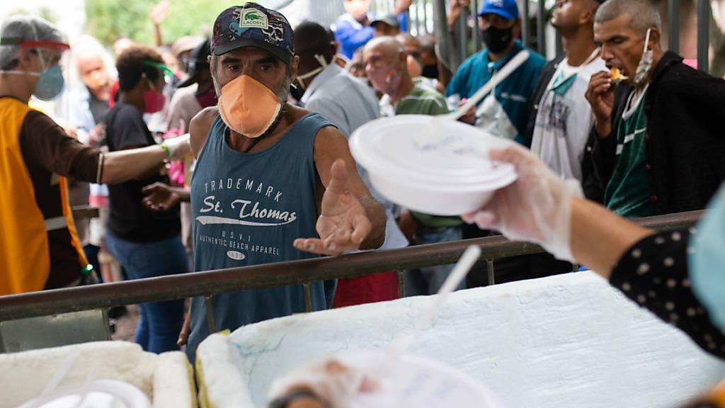 Zahlreiche Menschen stehen für eine Mahlzeit an, die von Freiwilliger der franziskanISCHE Initiative namens Sefras inmitten der Corona-Pandemie ausgegeben werden. Foto: Fernando Souza/dpa