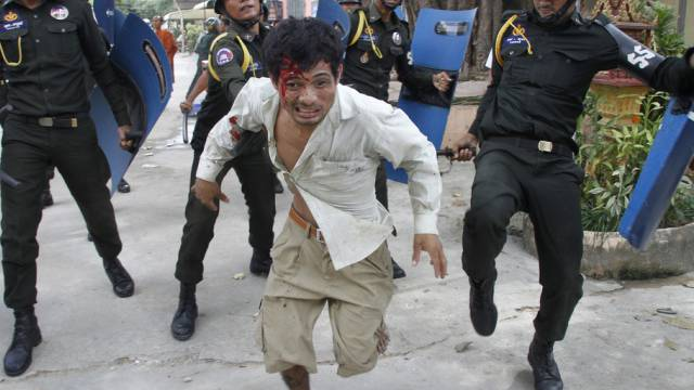 Polizisten verfolgen Demonstranten in Phnom Penh (Archiv)