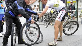 Urs Huber beim Radwechsel in Saas. Der Platten kostete ihn mit grosser Wahrscheinlichkeit den Titel. (Bild: Martin Platter)