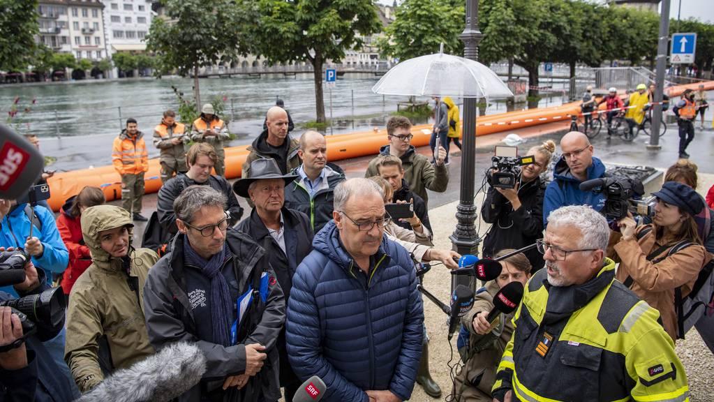 Der Bundespräsident Guy Parmelin, Mitte, und der Kommandant der Feuerwehr Luzern, Theo Hohnermann, rechts, bei seinem Besuch in Luzern. Die ersten Wasserübertritte an der Reuss in Luzern sind erfolgt, am Mittwoch, 14. Juli 2021, in Luzern. Der Wasserspiegel des Vierwaldstaettersees ist bedrohlich hoch angestiegen und es muss in den nächsten Tagen mit Überschwemmungen gerechnet werden.