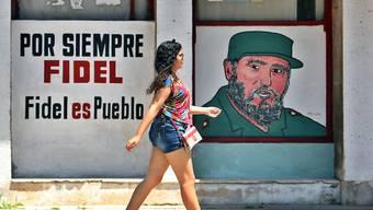 Für immer Fidel - Fidel ist das Volk. Die Kubanerin in Havanna scheint der Spruch an der Hauswand wenig zu beeindrucken.